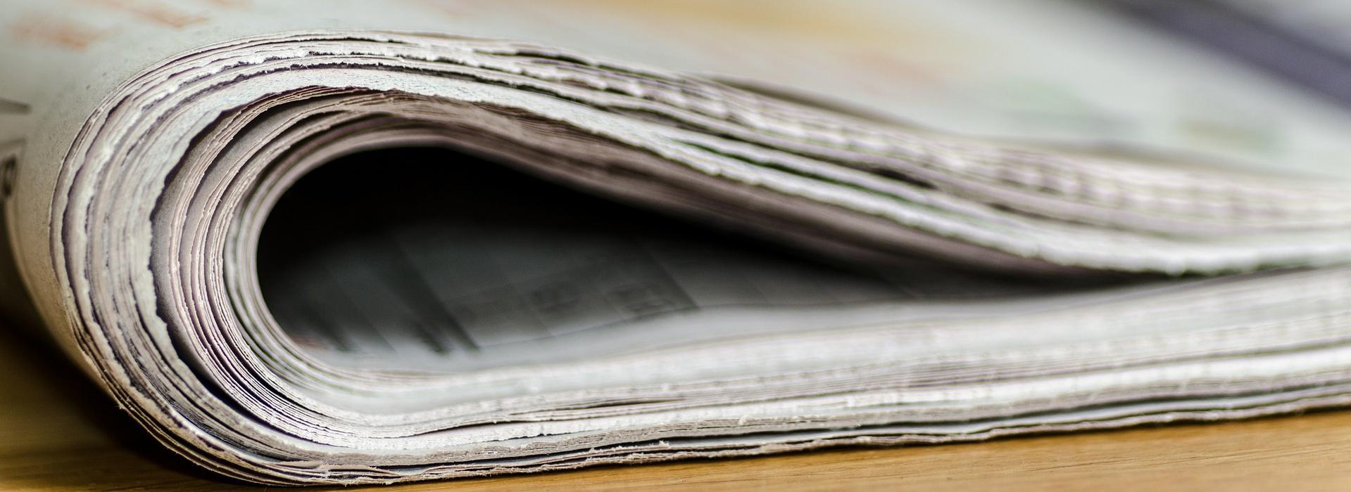 obere Kante einer zusammengefalteten Zeitung auf Tisch liegend Zeitungen_Stapel.jpg