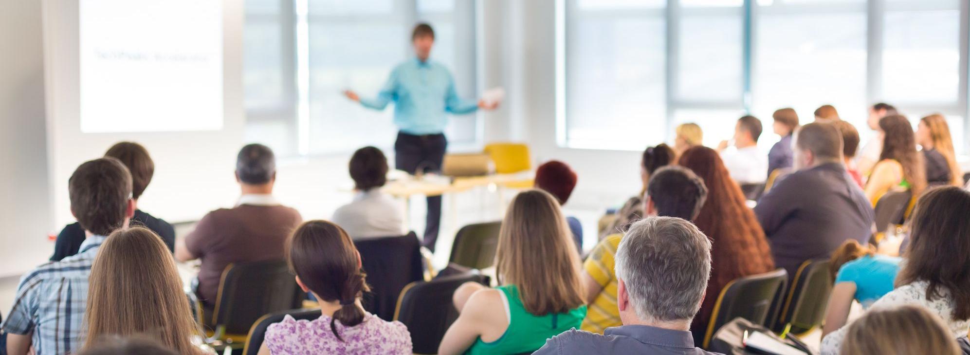Sprecher und eine Gruppe auf Stühlen sitzender Zuhörer Fotolia_67844411_Subscription_Monthly_XL.jpg