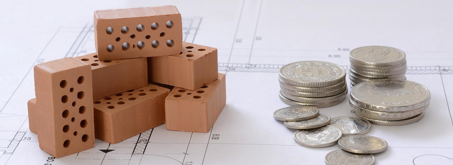 Bausteine und Geldstücke auf einem Plan Bauen_Geld.jpg