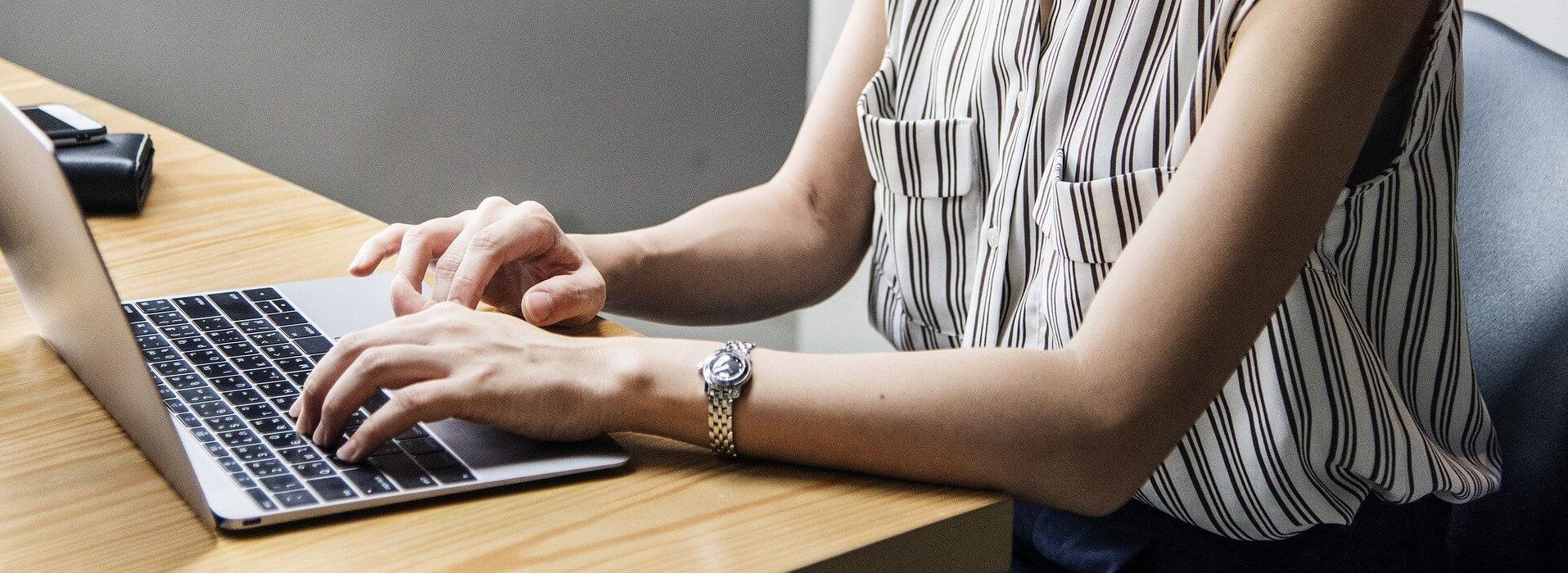 Frau auf der Tastatur eines Notebooks tippend header-bedienhinweise.jpg
