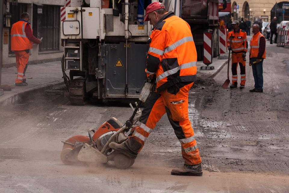 Bauarbeiter schneidet mit einer Steinsäge den Asphalt einer Straße